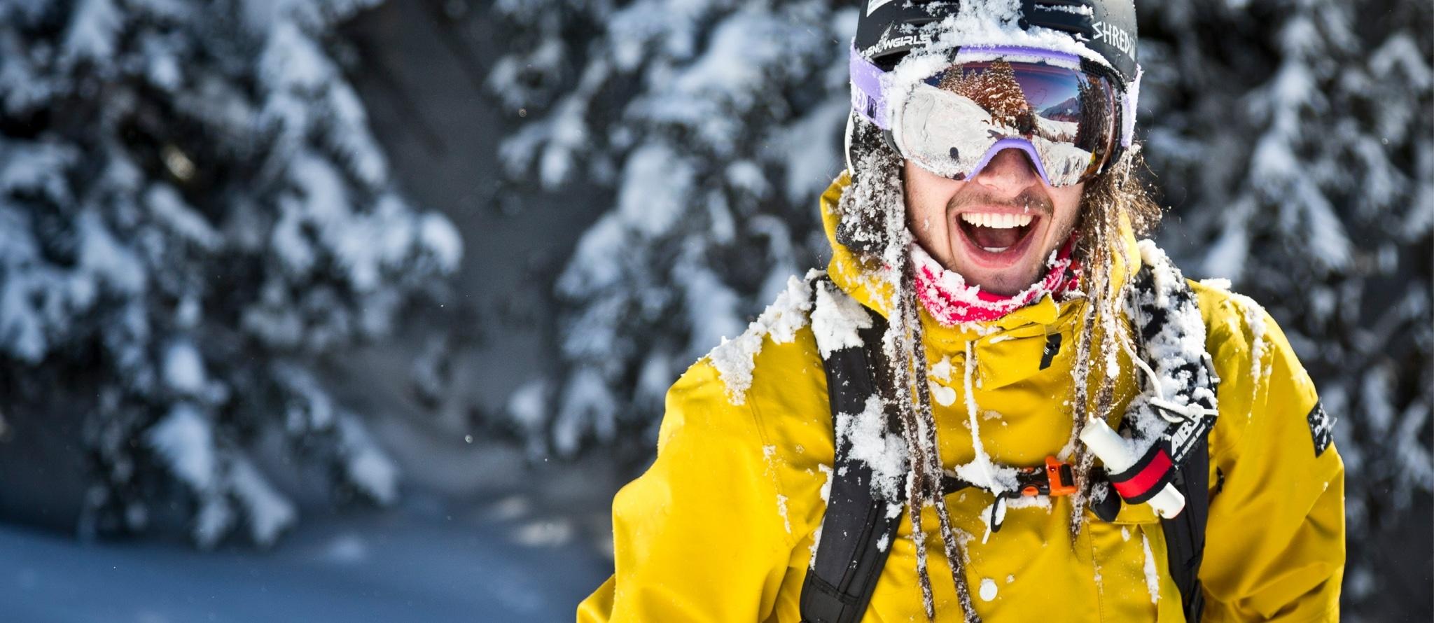 Ein Mann mit gelber Ski-Jacke und Skihelm