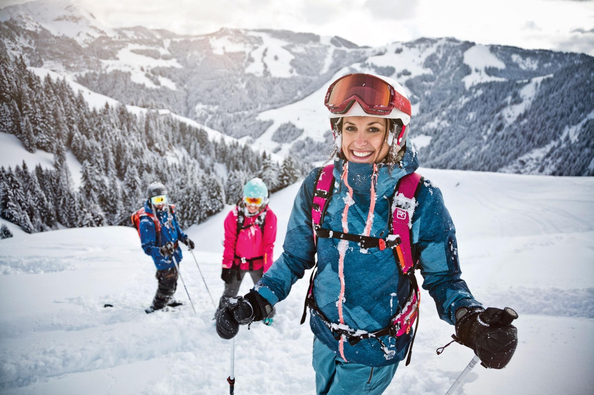 Frau im Skianzug lächelt in Kamera