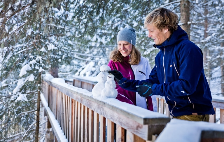Paar steht auf Brücke und baut Mini-Schneemann