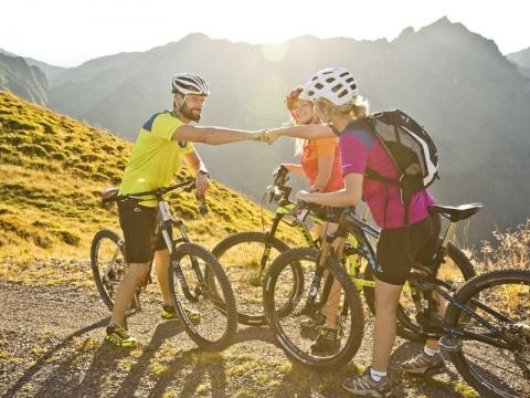 Radfahrer stehen zusammen und geben sich die Faust