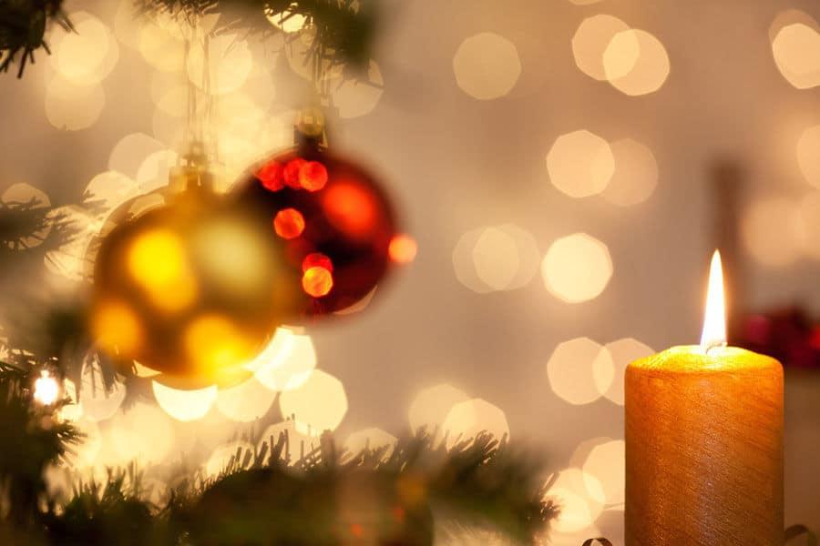Kerze brennt im Hintergrund hängen Christbaumkugeln