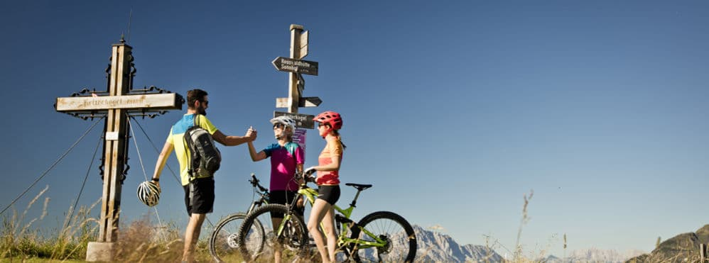 3 Radfahrer stehen vor Wegweiserschild