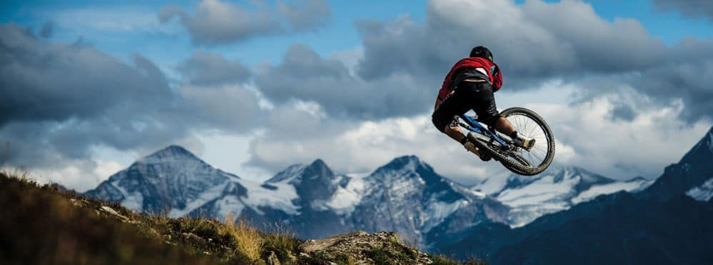 Biker macht Stunt vor Bergpanorama