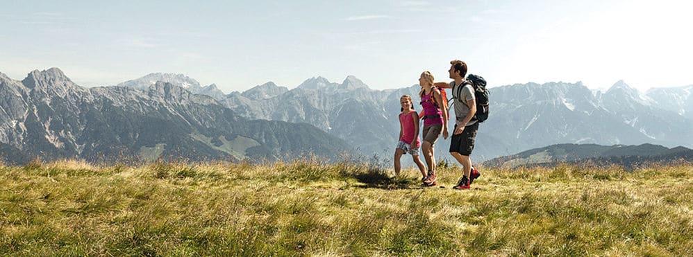 Familie beim Wandern mit Bergpanorama im Hintergrund