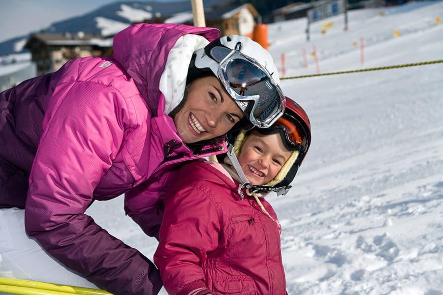 Mutter mit Kind in Skianzug im Winter