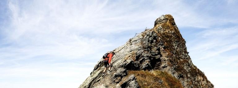 Mann klettert auf steilen Fels hinauf