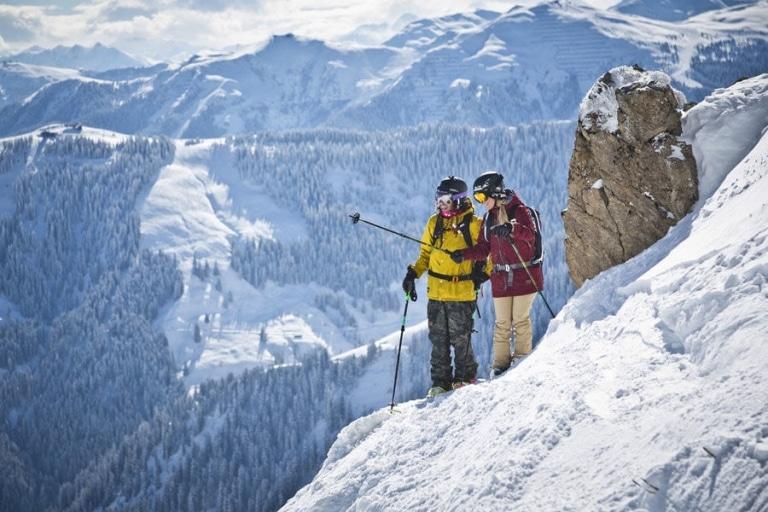 Paar steht auf steilem Schneehang mit Skiern