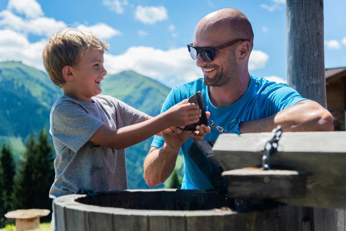 Vater und Sohne blödeln bei Wasserspender herum