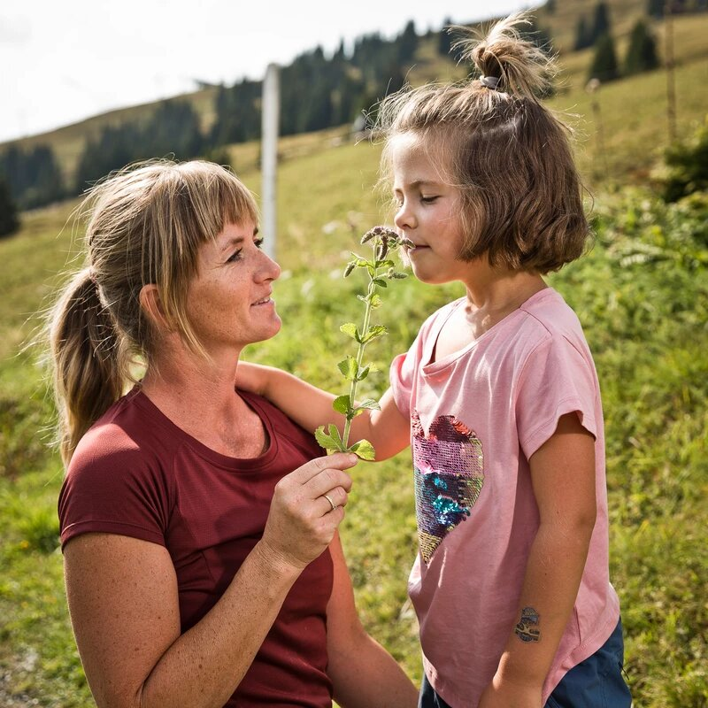 Mama mit Mädchen auf Wiese hält ihrer Tochter Blumen zum Riechen hin
