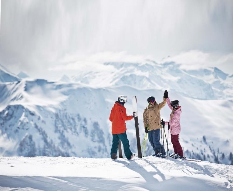 3 Skifahrer vor Bergpanorama