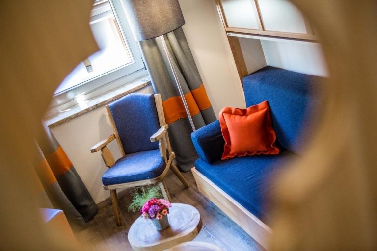 Blauer Stuhl neben blauen Sofa mit orangem Polster