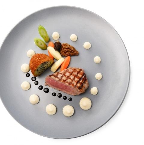 Schön angerichteter Teller mit Fleisch, Gemüse und einer Sauce