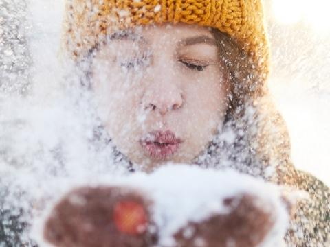 Frau mit oranger Mütze pustet Schnee in Kamera