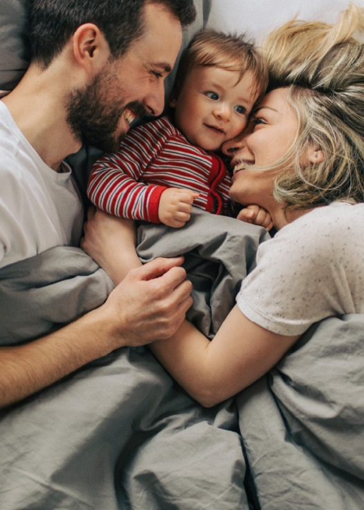 Eltern mit Kleinkind kuscheln im Bett