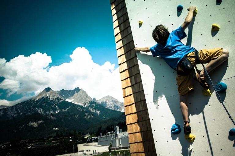 Junge klettert auf Outdoor Kletterwand