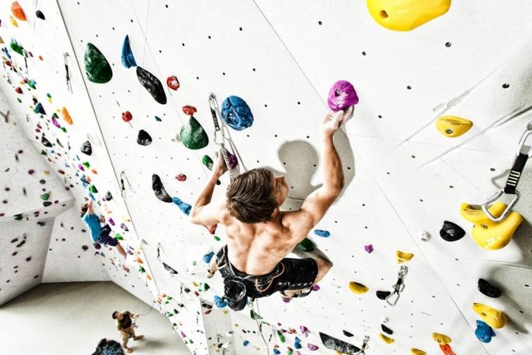 Junger Mann klettert oben ohne auf Indoor Kletterwand