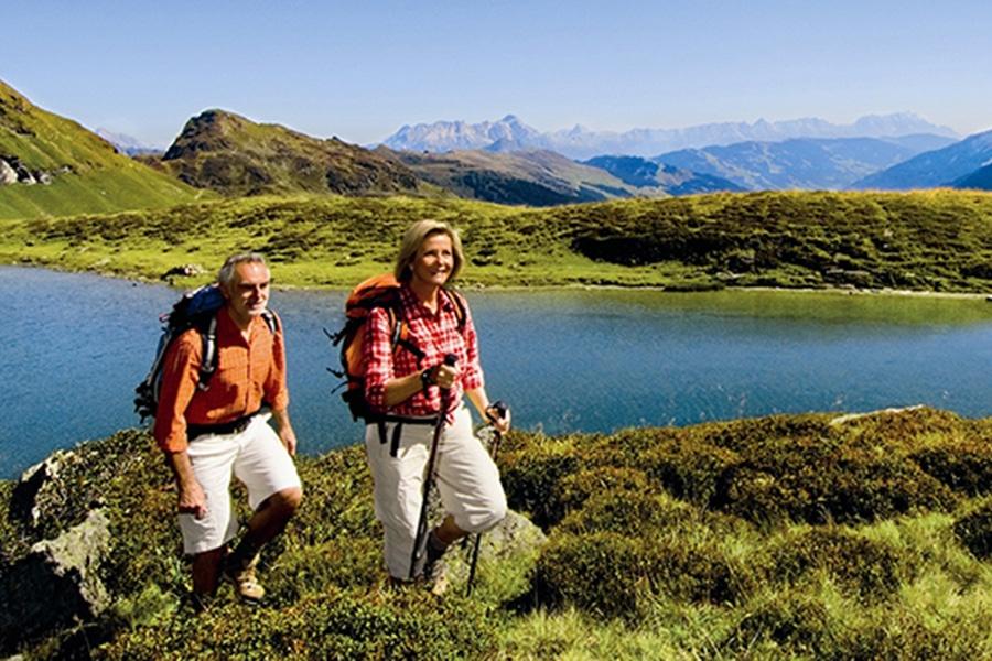 Älteres Paar beim Wandern im Hintergrund ist ein Bergsee