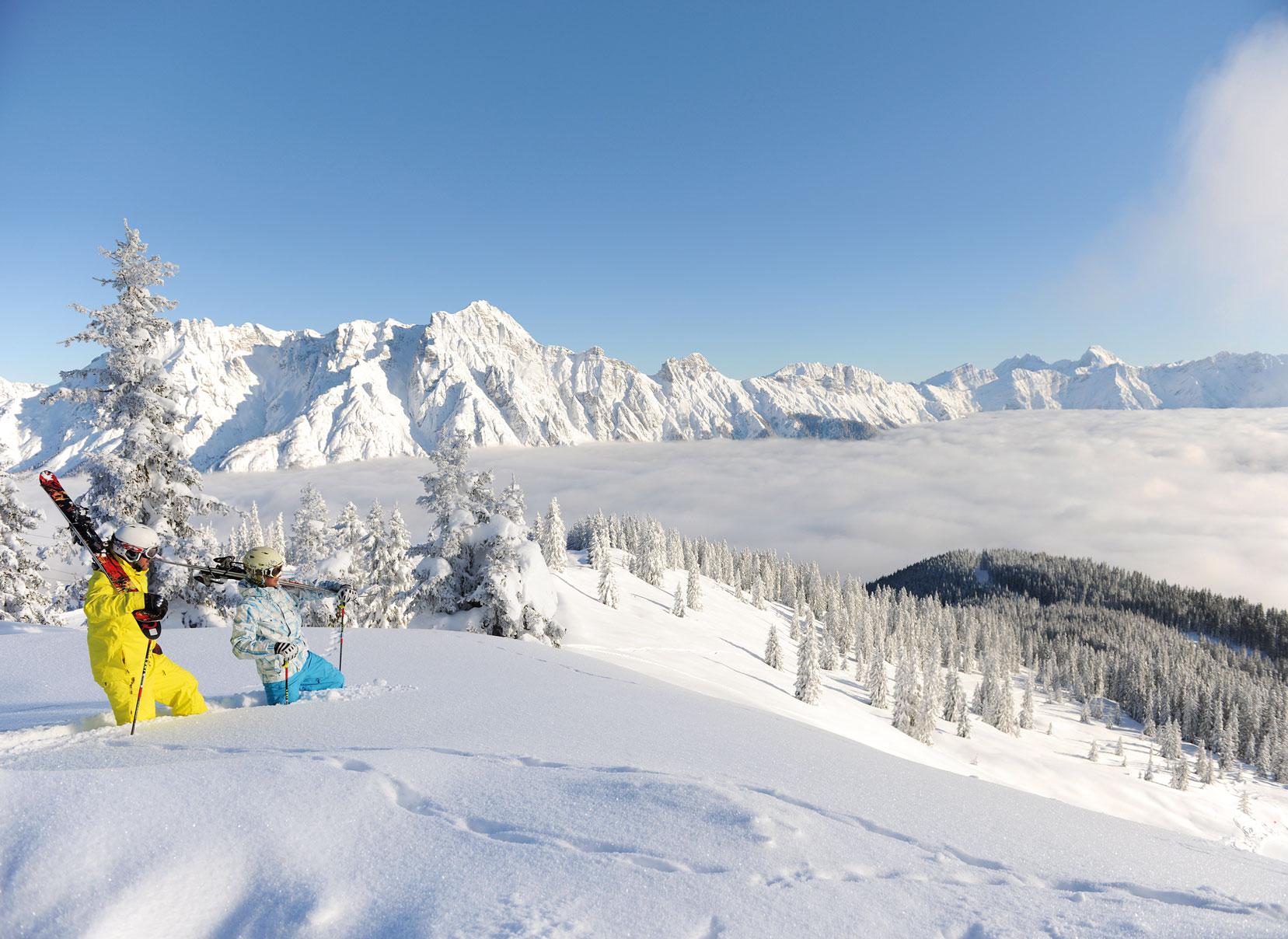 Paar wandern mit Ski auf den Schultern durch Tiefschnee