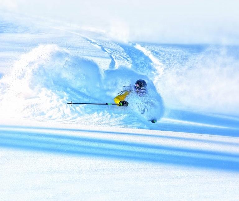Skifahrer fährt Tiefschnee hinunter