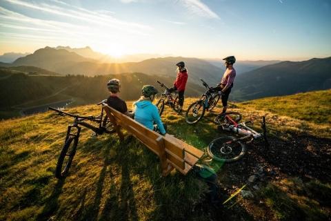 4 Mountainbiker ruhen sich auf Bank aus und bewundern Sonnenuntergang