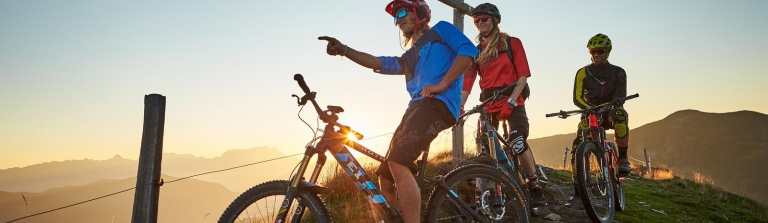 3 E-Biker fahren bei Sonnenuntergang über Wiese