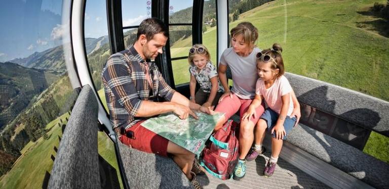 Familie in Sommerbahn-Gondel schaut auf Karte