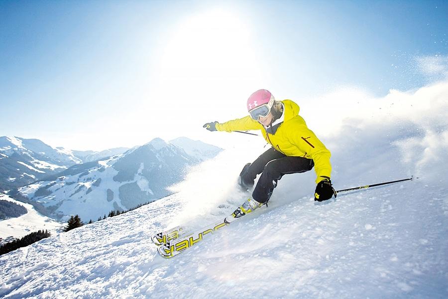 Frau fährt auf Skiern Hand hinunter