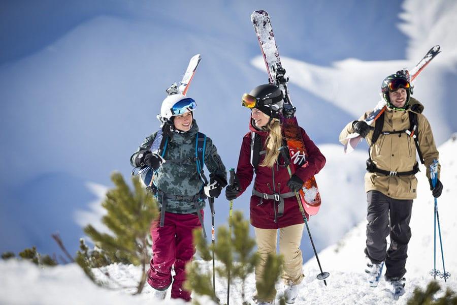 3er Gruppe geht beschneiten Hang hinauf mit Skiern auf den Schultern