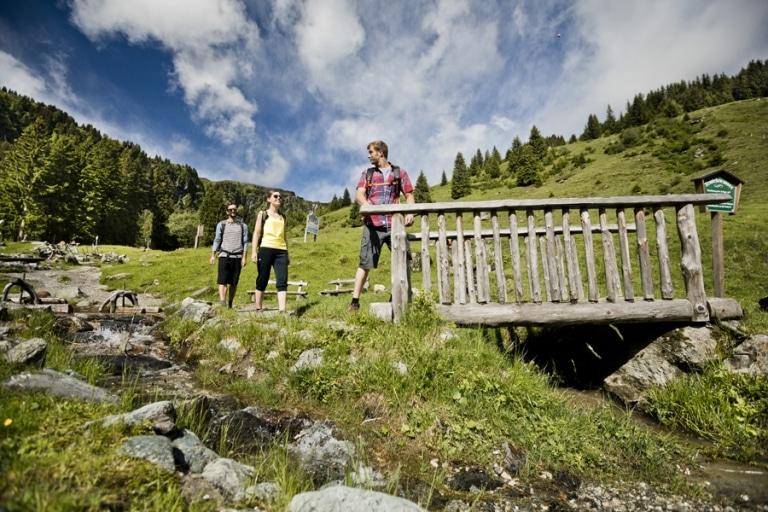 3 Freunde beim Wandern während sie Brücke überqueren