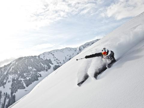 Skifahrer fährt steilen Schneehang hinunter