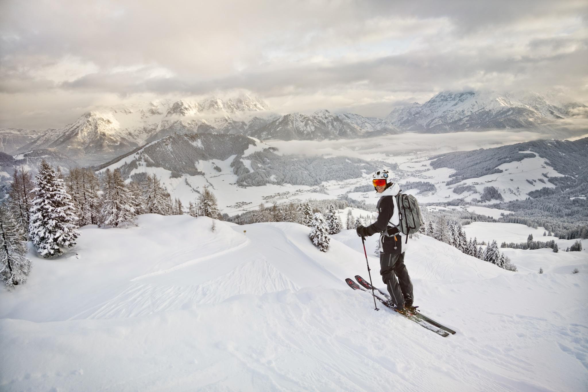 Person auf Skiern vor verschneiter Bergkulisse