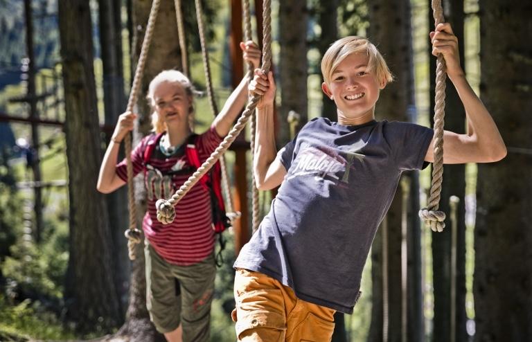 2 Kinder im Klettergarten halten sich an Seilen