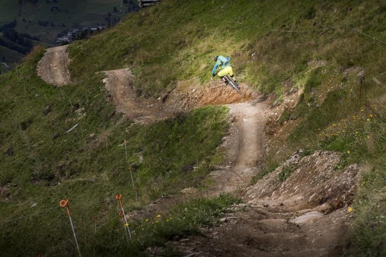 Mann springt gemeinsam mit Rad über Hügel