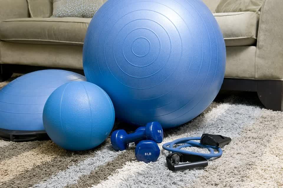 Blaues Fitnessequipment Medizinball, Gymnastikball, Springseil, Hanteln liegt auf grauem Flauschteppich