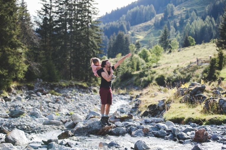 Vater trägt Mädchen auf Schulter und zeigt mit der Hand in die Ferne