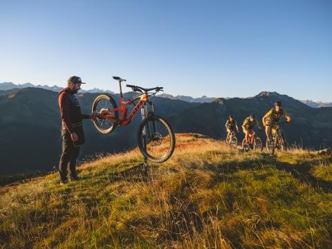 Mann hebt Fahrrad mit einer Hand auf im Hintergrund kommen 3 Mountainbiker den Berg hinauf