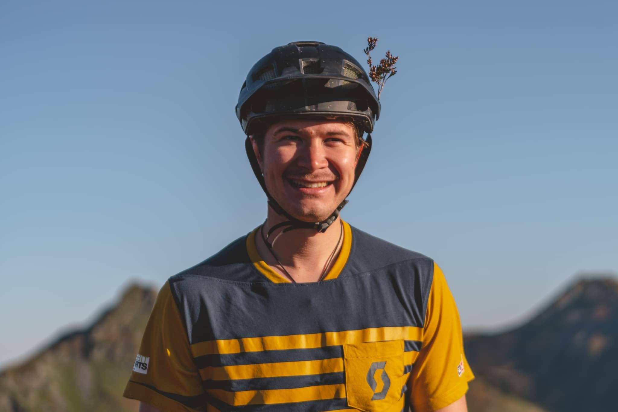 Junger Mann mit Fahrradhelm grinst in Kamera