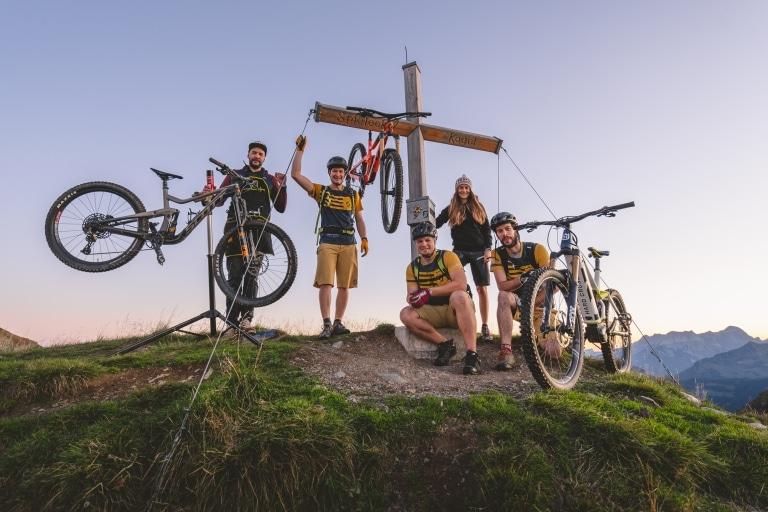 4 Leute posieren mit 2 Mountainbikes vor Gipfelkreuz