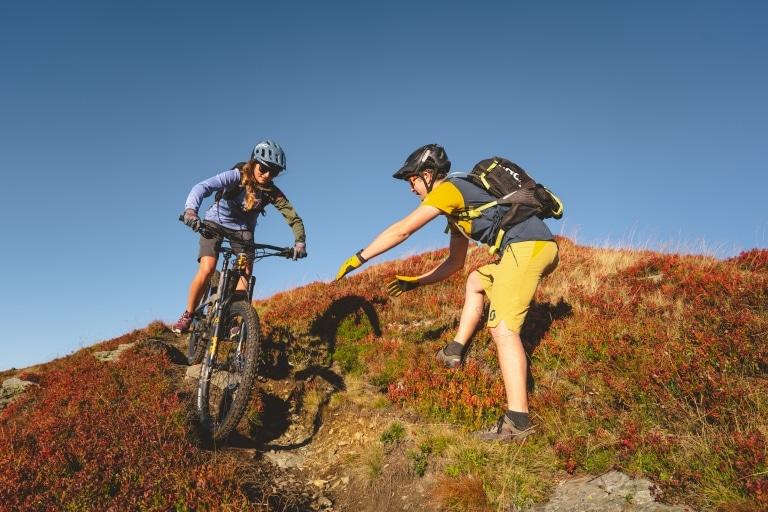 Frau auf Fahrrad wird von Mann trainiert