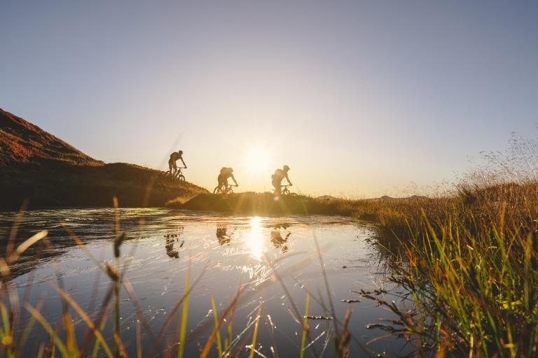 3 Mountainbiker fahren bei Sonnenuntergang Hand hinunter im Vordergrund ist ein See zu erkennen