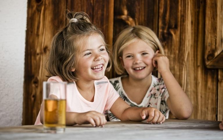 2 Mädchen sitzen lachend an Tisch