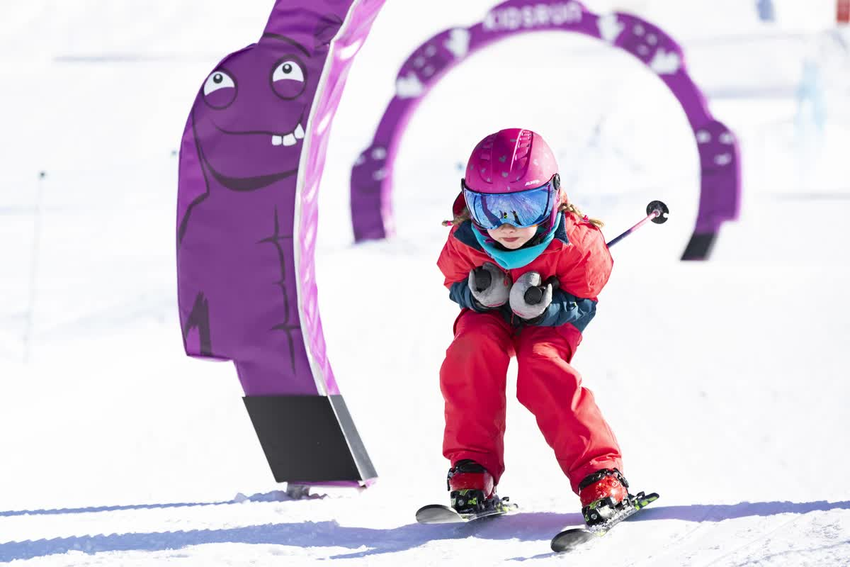 Mädchen in rotem Skianzug fährt Schneepflug