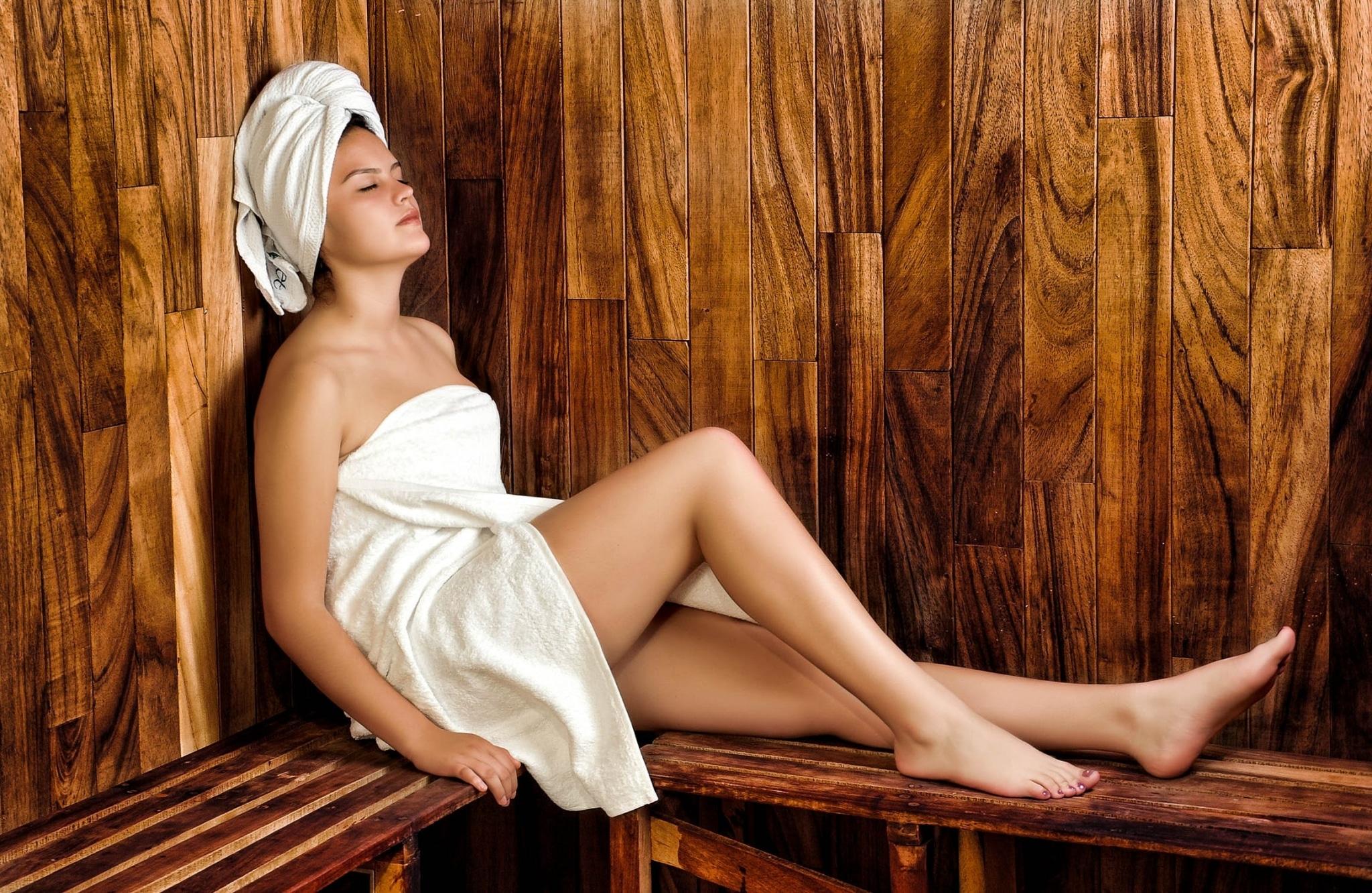 Frau in Handtuch gewickelt sitzt in Ecke von Sauna und hat Augen geschlossen