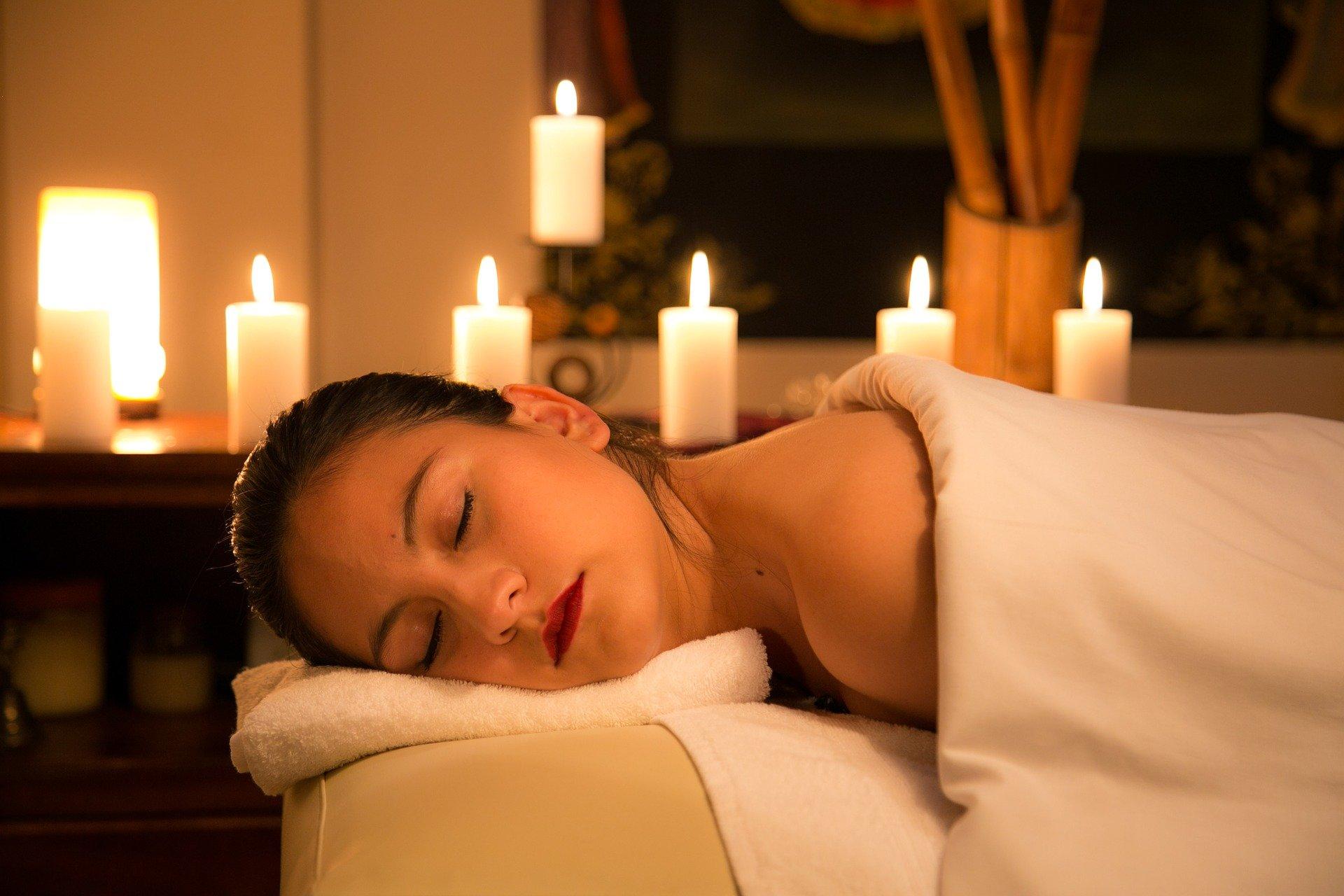 Frau entspannt auf Liege im Hintergrund brennen Kerzen