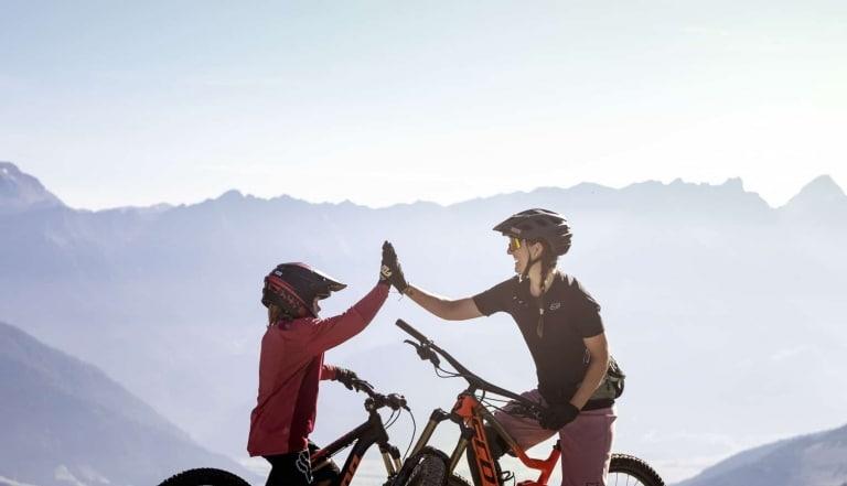 Mutter und Kind auf Fahrrädern geben sich High-Five