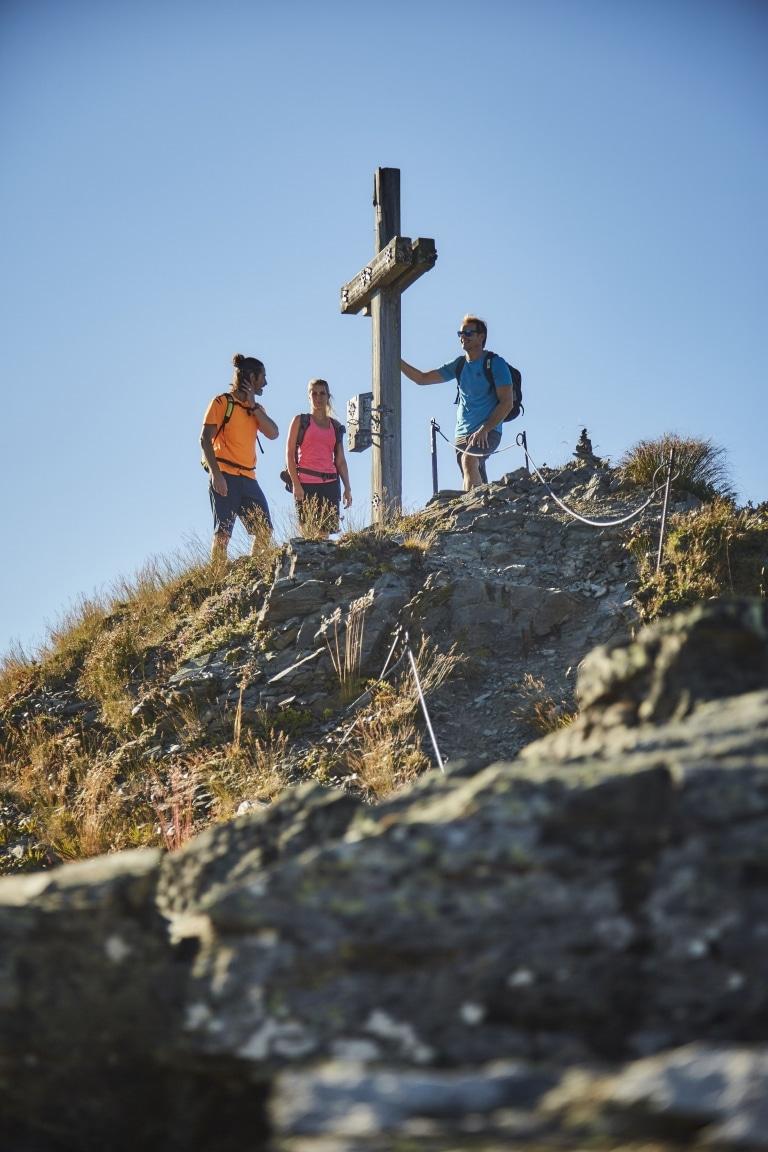 3 Wanderer stehen bei Gipfelkreuz