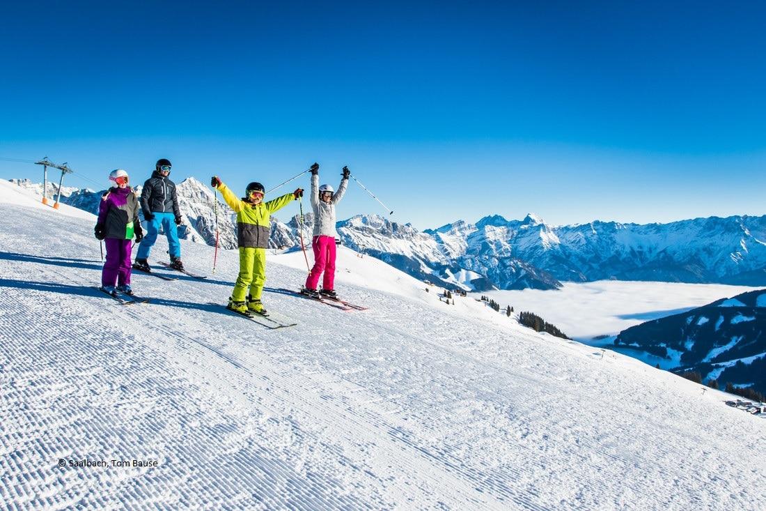 4 Kinder fahren mit Skiern einen beschneiten Berghang herunter