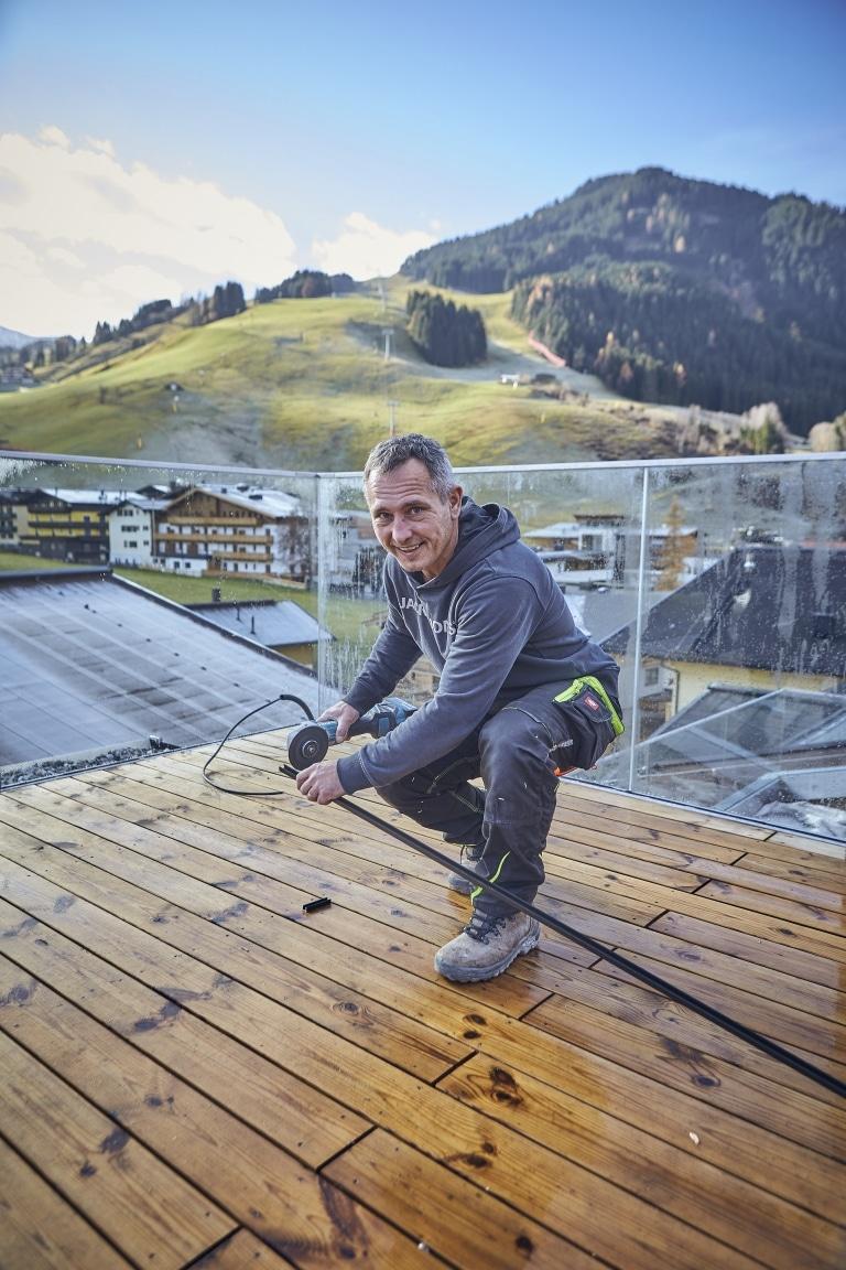 Mann beim Verlegen von Dachterrasse