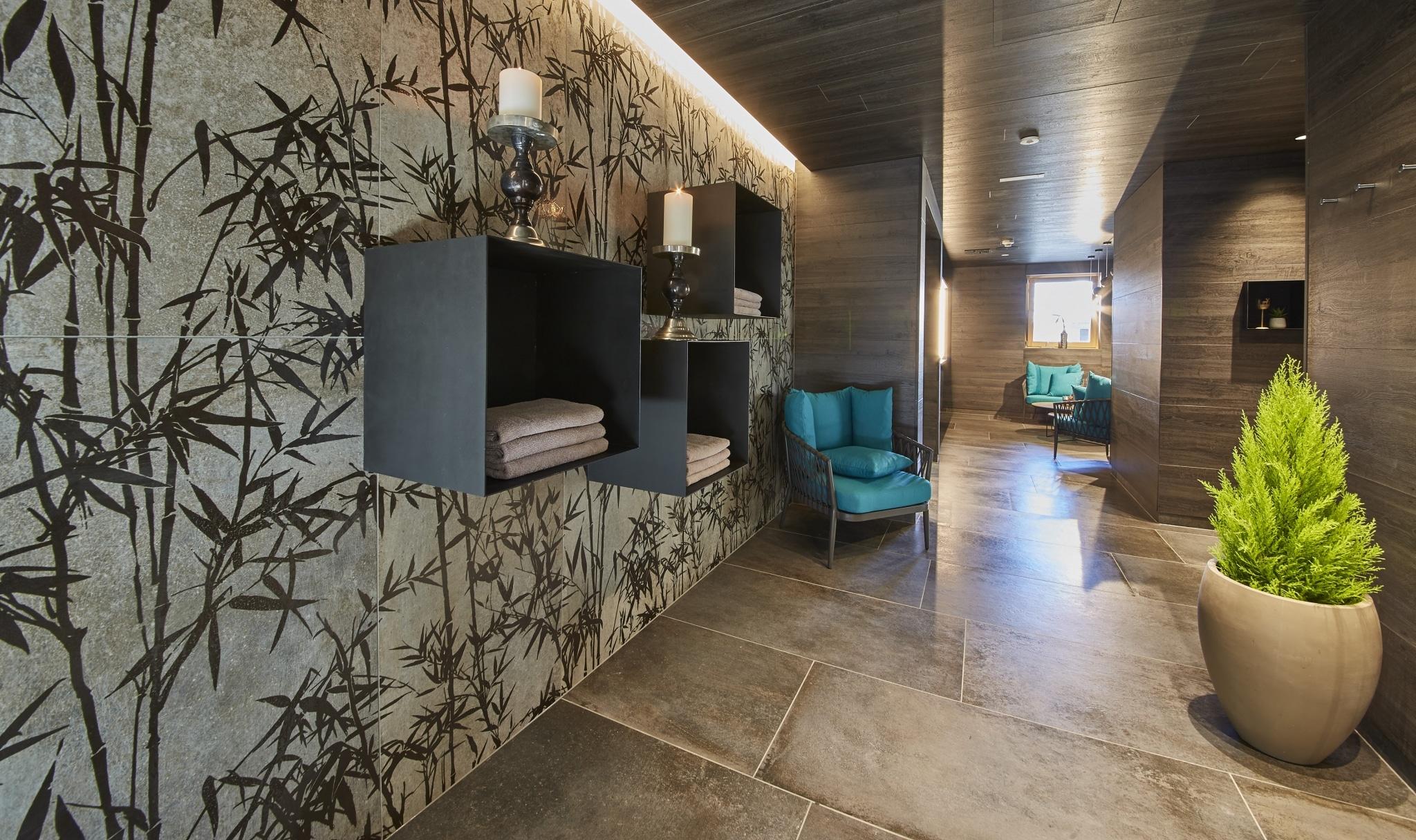Spa Bereich mit Stühlen, Wanddekorationen und einer grünen Pflanze