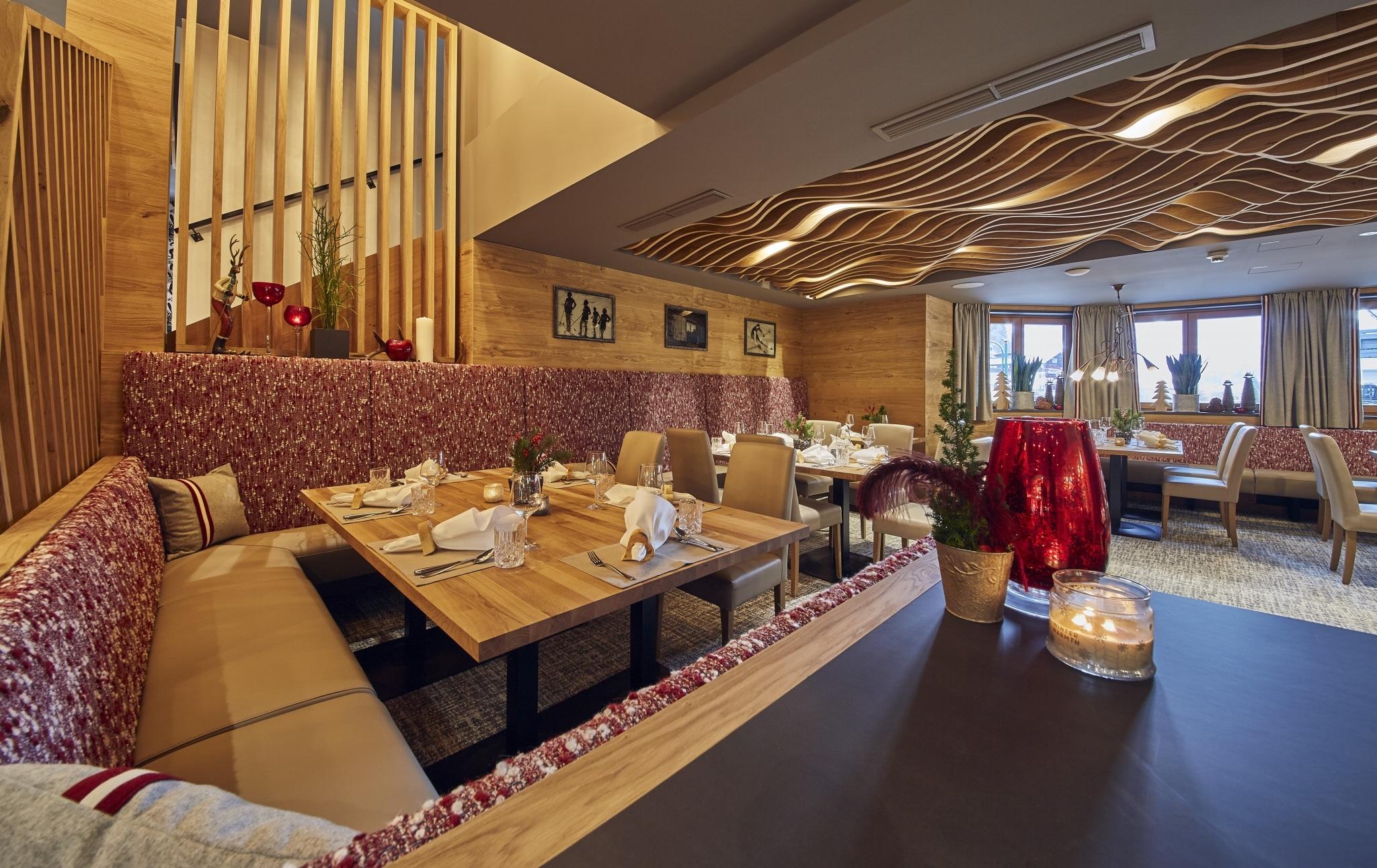 Ein gedeckter Tisch mit Dekoration und rot gemusterter Eckbank-Polsterung